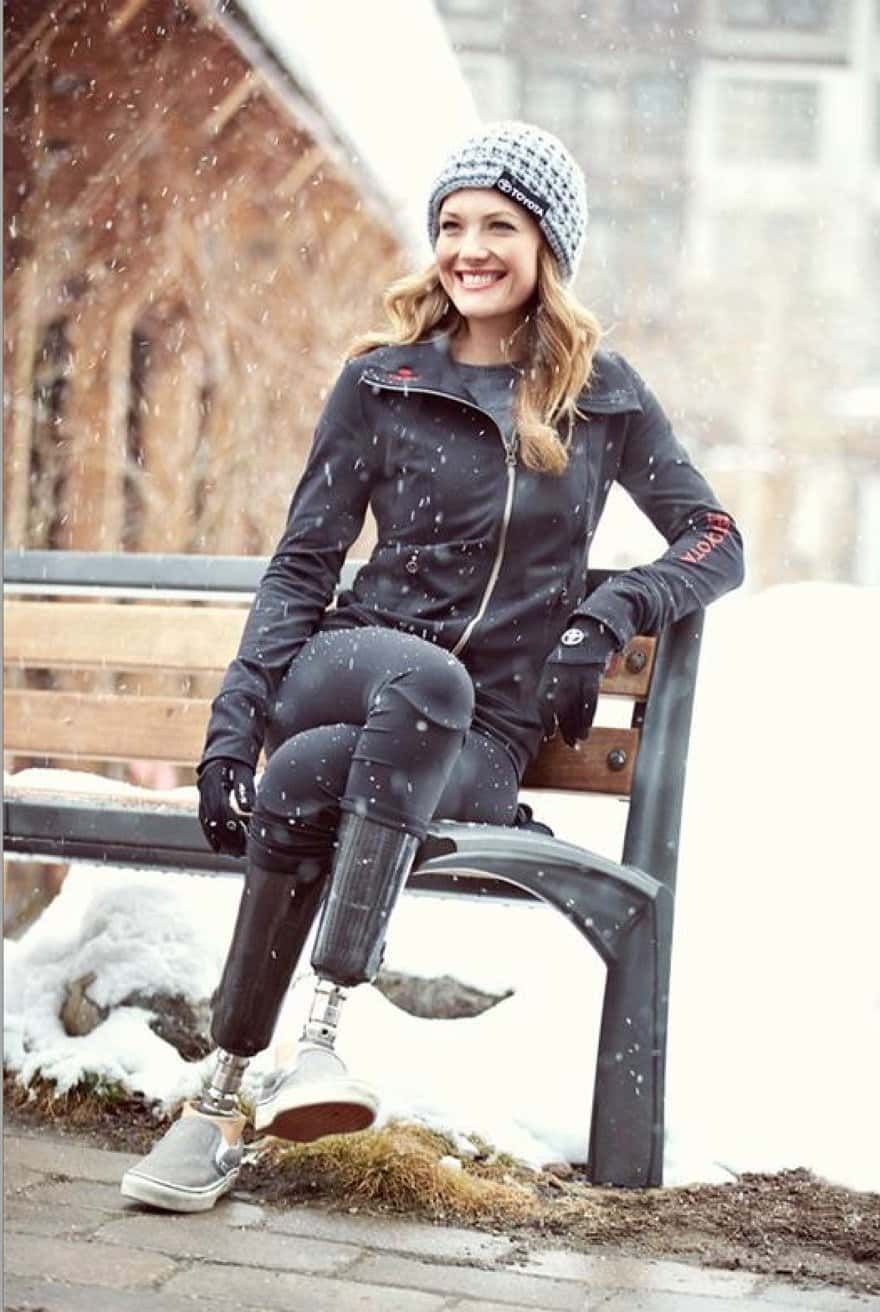 Amy Purdy sits on a bench as the snow falls. Wearing black leggings and zip up toyota jacket and gray toyota beanie