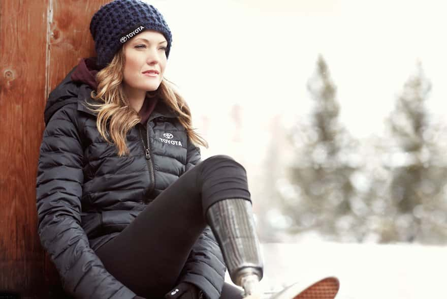 Amy Purdy dons a black toyota puffy jacket and matching navy blue beanie. Makeup is soft with a sunkissed cheek soft brown eyes and barely there pink lip gloss