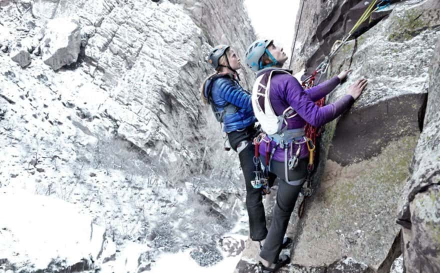 Climbers wearing blue and purple puffers and black climbing pants