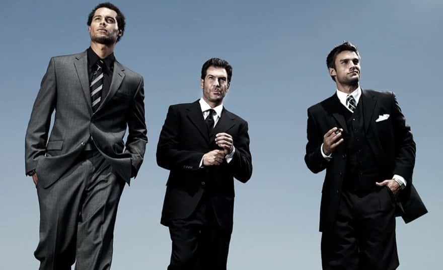 three dark ahird men in black and gray business suits for ad campaign for Gilettesuits