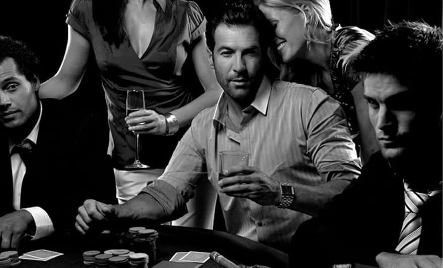 Black and white photo with a Dark haired man palying poker with his girlfriend. five o'clock shadow