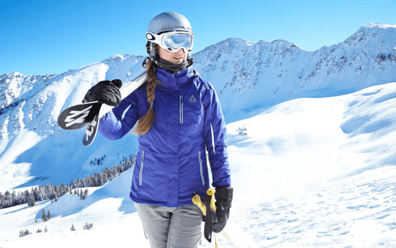 blond Female in braids carrying her skis wearing a cobalt blue ski jacket and gray ski pants