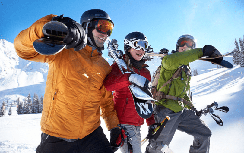 Friends carrying skis wearing gold, red and lime green ski jackets and ski pants