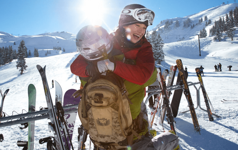 Couple having fun in the mountains wearing a red ski jacket and a lime green ski jacket and ski pants