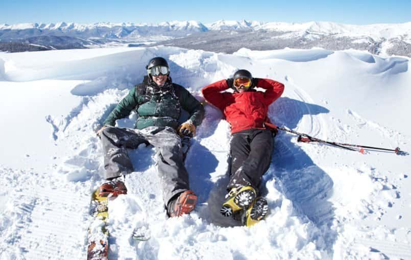 two male skiiers hanging out in the snow in Green and Red ski jackets and gray and black ski pants. Vail, CO. Primaloft