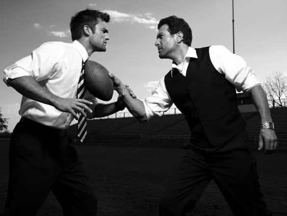 Two men in formal white-collar shirts face each other, an American football between them