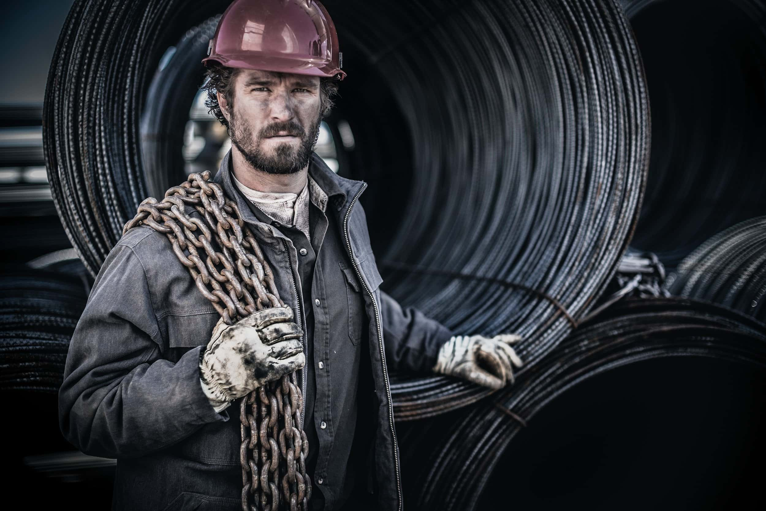 rugged man carrying chains wears a hard hat and distressed jacket, gloves and shirt