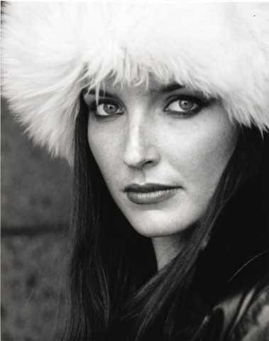 black and white photo of a dark haired woman wearing. FUR HAT. BOLD SMOKEY BLACK EYES AND A BOLD RED LIP
