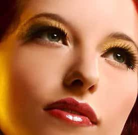 Woman's face with red, glossy lips, gold eyeshadow, and pointed eye lashes