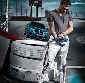 Man donning blue gloves, driver's suit, and sunglasses  in front of a blue BMW at a car race track