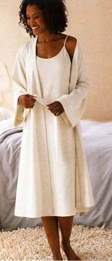 African-American woman smiling as she wears a white bathrobe and white night gown