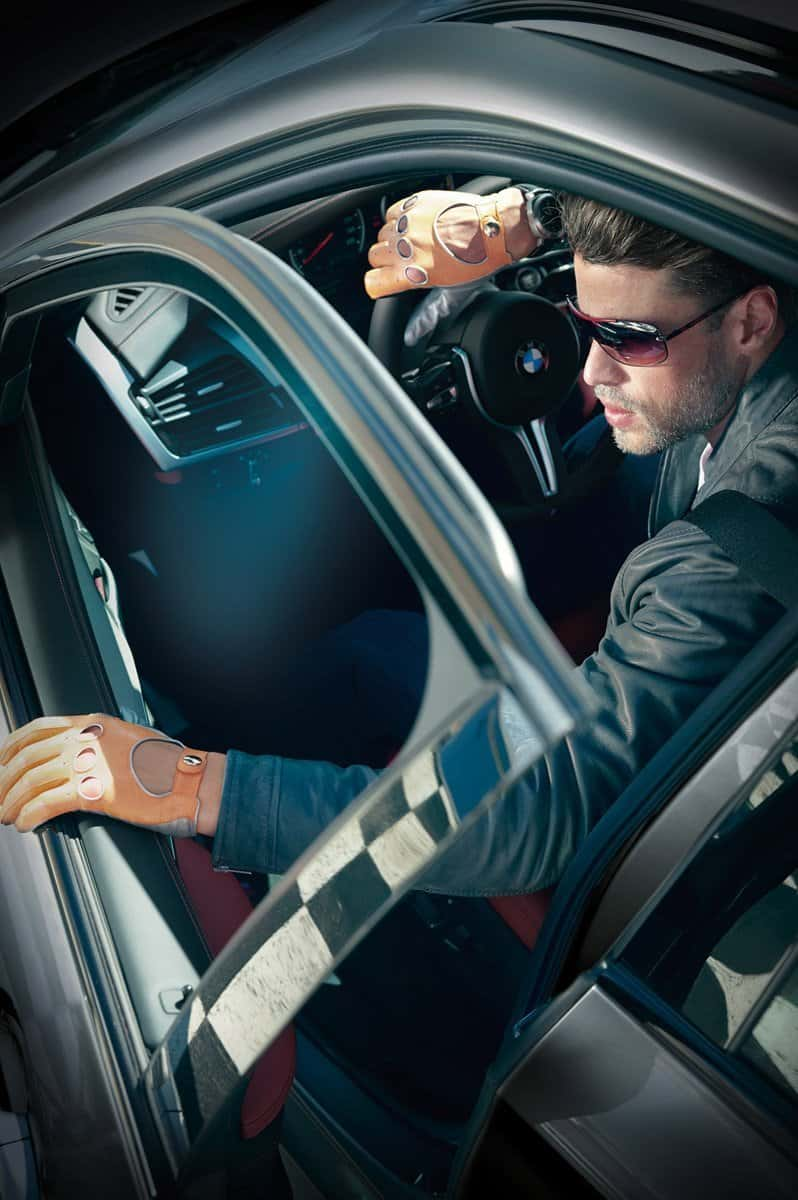 Model poses as a race care driver wearing leather gloves, jecket and shades for BMW photo shoot