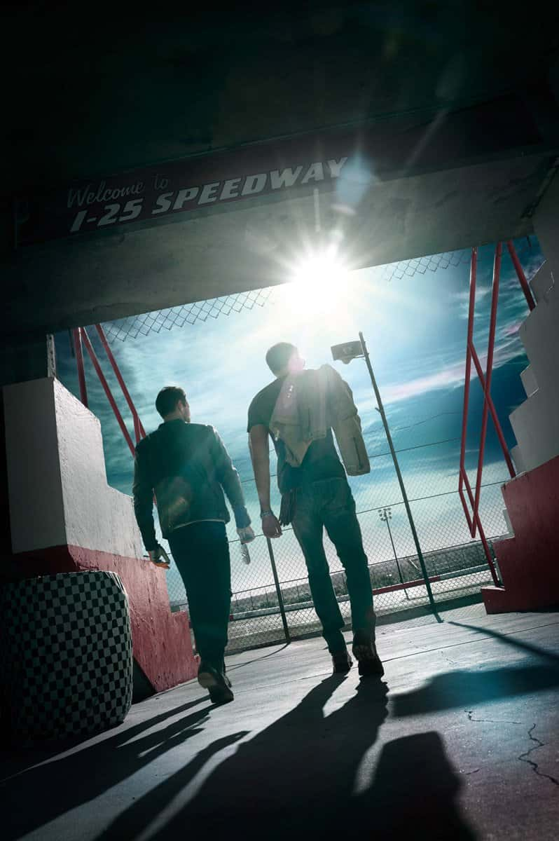2 men wlking through corridor on their way to the race track. Wearing leather jackets for a BMW shoot