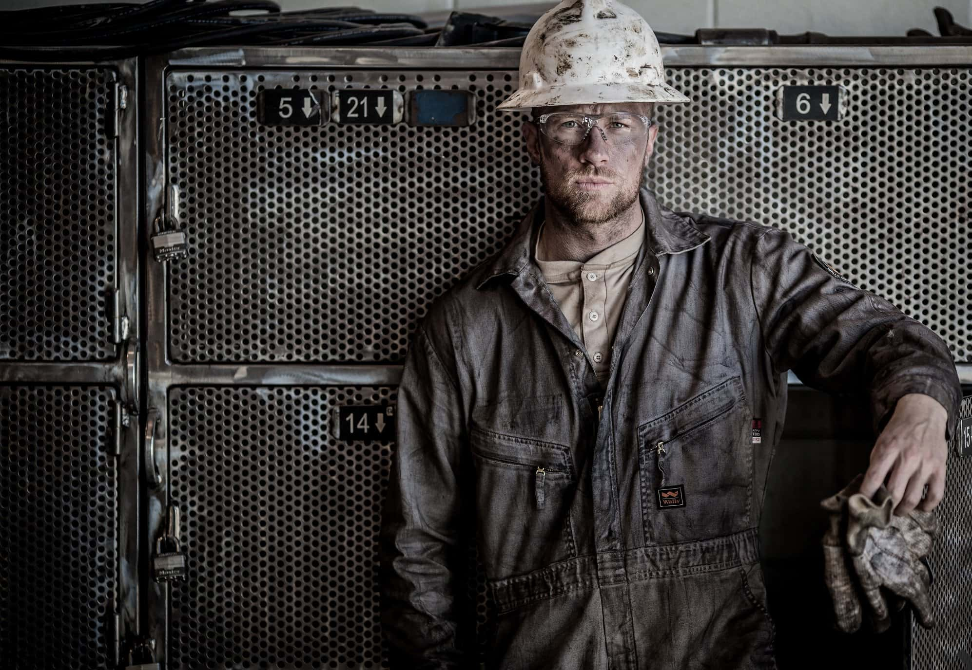 Oil rig model wears a day of dirt on his face and distressed hard hat, henley and work coveralls