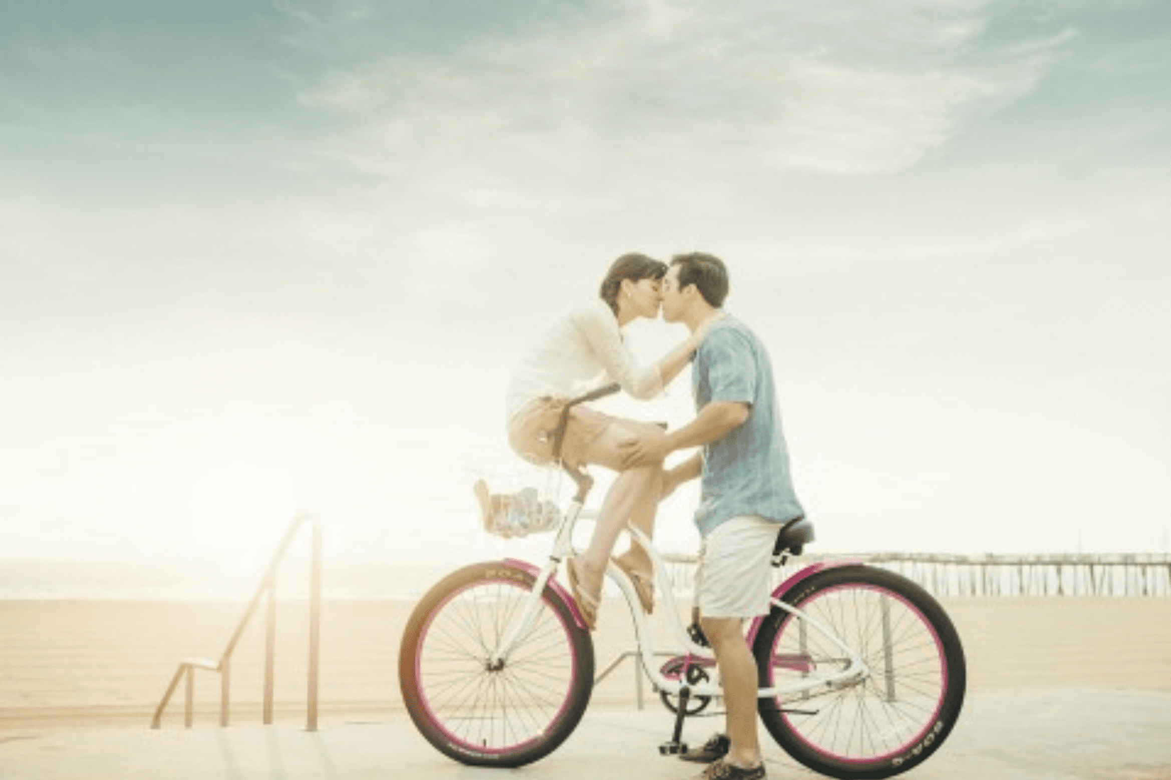 Couple kissing on a bike on Virginia Beach,Virginia wearing light weight button down shirts and shorts.