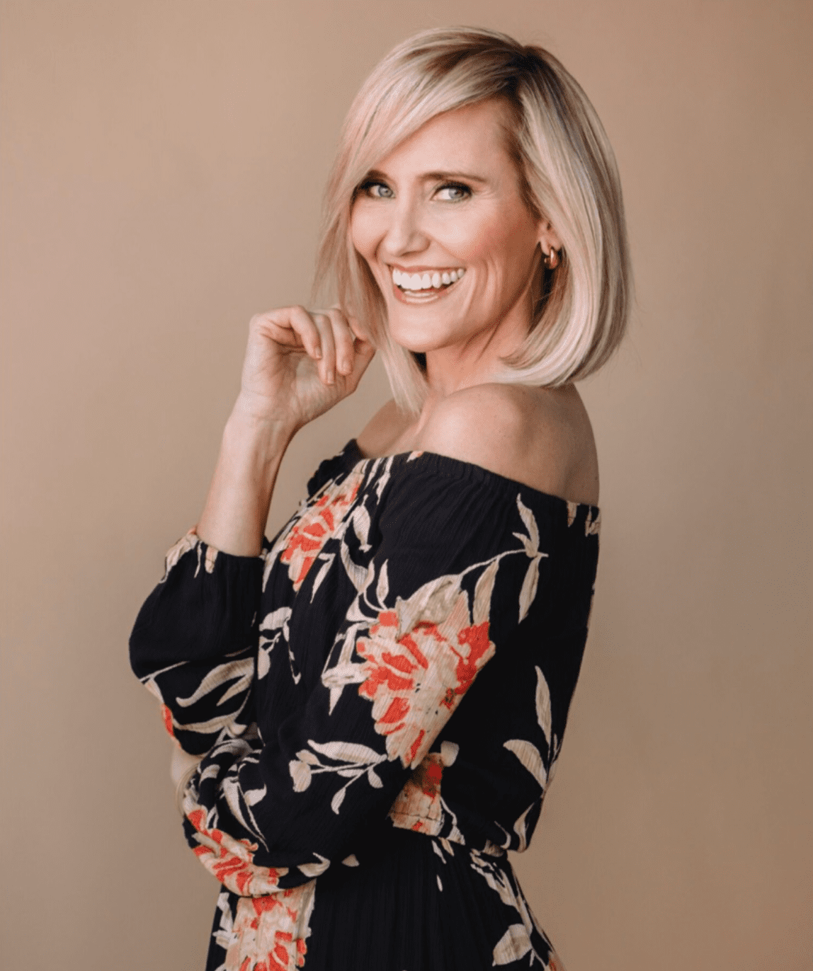 Blond-haired model wearing an off-the-shoulder, flower-printed blouse