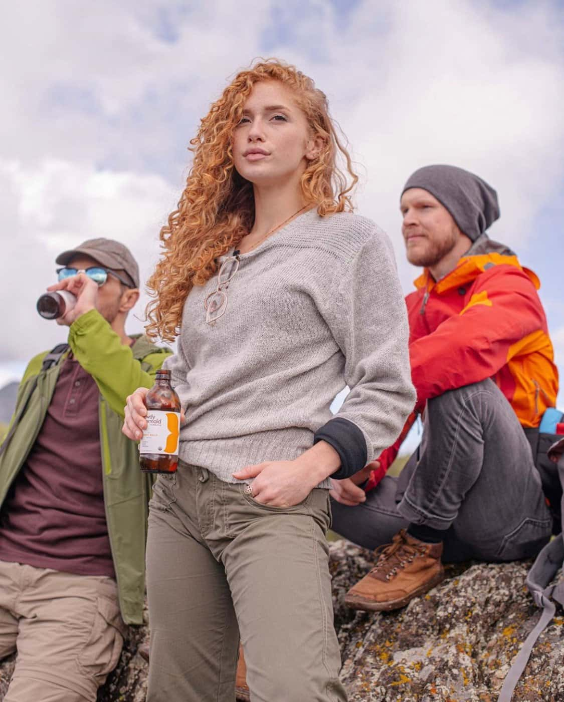 long red curly hair female wearing a gray hooded sweater and army gree pants drinking a kambucha with her male friends in redand ornge rain jacket and green zip up jacket over a burgundy henley