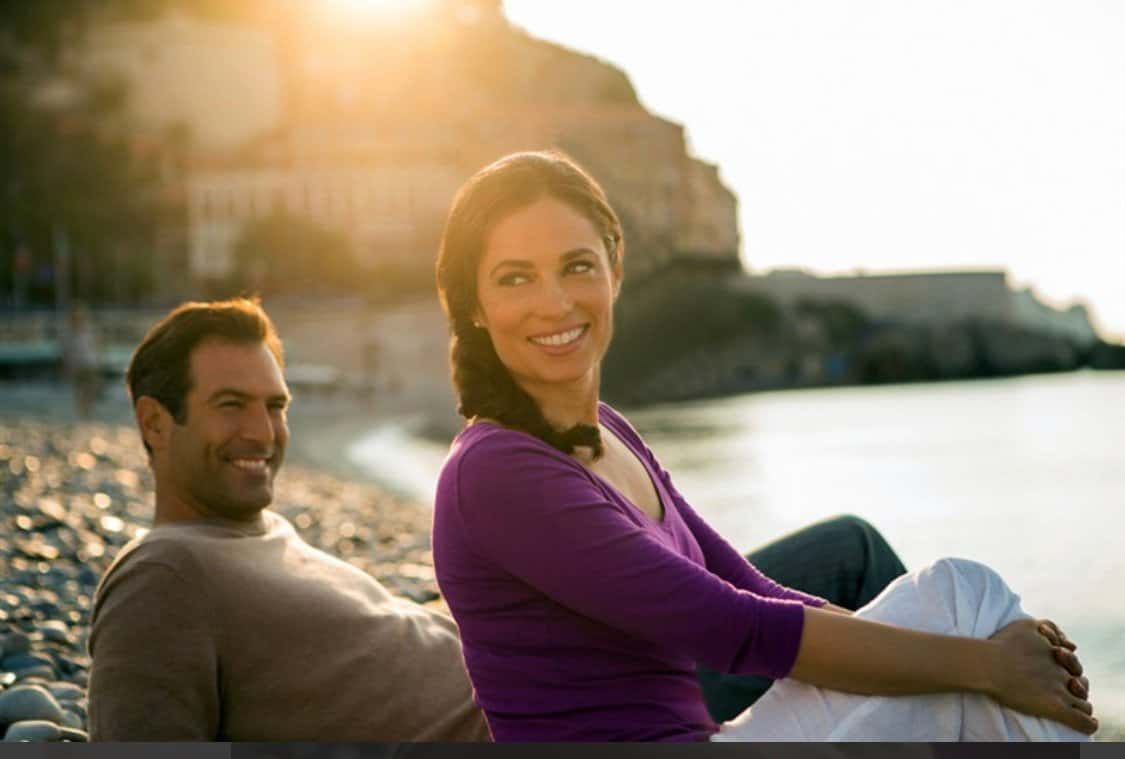 dark haired couple on the beach. Women in purple shirt and white jeans. Man leaning back ina cream light weight sweater